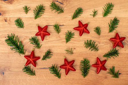 Christmas background with fir tree, red shiny stars on brown wooden table. Top flat view with copy space.