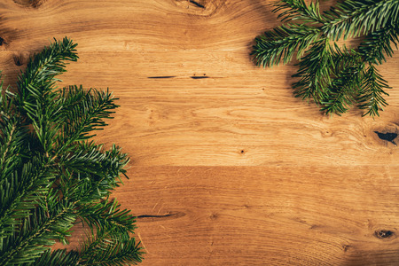 Christmas background with fir spruce tree, blank frame on brown wooden table. Top flat view with copy space. Imagens