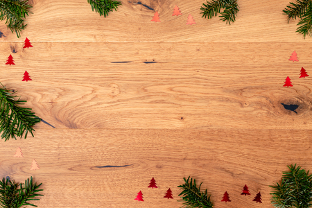 Christmas background with fir tree, red shiny trees on brown wooden table. Top flat view with copy space.