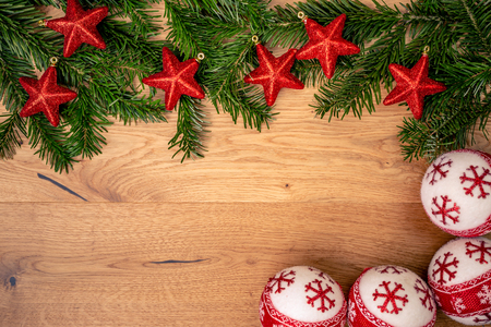 Christmas background with fir tree, red stars and christmass balls on brown wooden table. Top flat view with copy space.