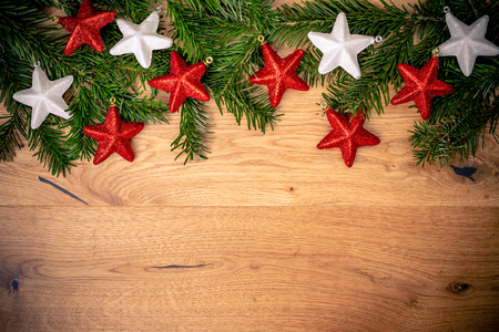 Christmas background with fir tree, red and white shiny  stars on brown wooden table. Top flat view with copy space.