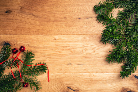 Christmas background with fir tree, red shiny bells on brown wooden table. Top flat view with copy space.