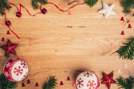 Christmas background with fir tree, red stars and christmass balls on brown wooden timber board. Top flat view with copy space. Imagens