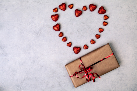 Gift or present for Valentines Day in brown paper box with red hearts. Love concept over gray background. Top view. with copy space.