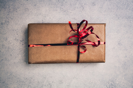 Gift or present in brown paper box with red ribbon, above view. Top centered closeup view with copy space.