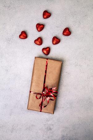 Gift or present in brown paper box with red hearts. Love concept over gray background. Top view. with copy space.