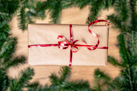 Christmas gift on wooden board with fir tree. Red ribbon on paper gift box. Top closeup view with copy space.