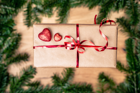 Gift or present in brown paper box with red hearts. Love concept over green background. Top view. with copy space.