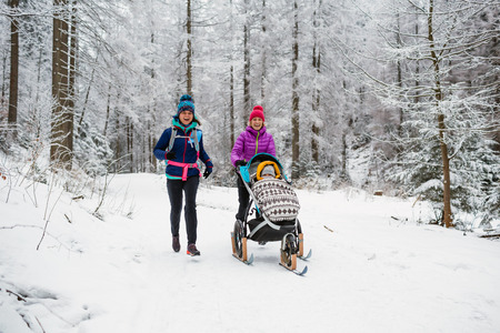 Mother with baby stroller enjoying winter forest with female friend or partner, family time. Hiking and running woman with sledge pram, teamwork concept. Beautiful winter inspirational mountains.