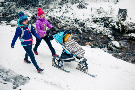 Two women with baby stroller enjoying motherhood in winter forest, mountains landscape. Mother hiking with a partner and a child in white snowy woods. Beautiful winter inspirational mountains. Imagens