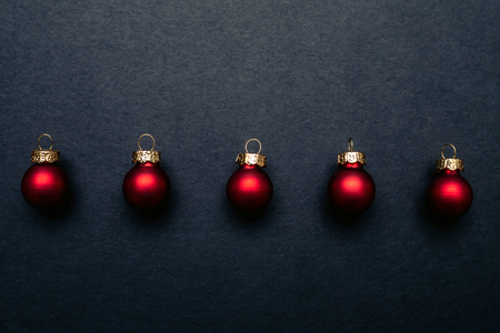 Christmas red shiny balls flat layout on dark background. Top closeup view with copy space.
