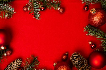Christmas red background with fir tree, red christmass balls frame. Top flat view with copy space. Imagens