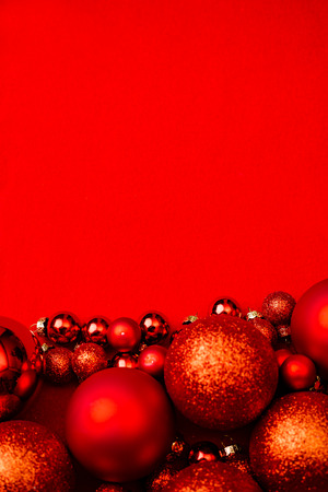 Christmas red background frame with red christmas balls. Top flat view with copy space.