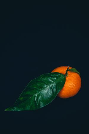 Ripe tangerine with green leaf on black vintage background