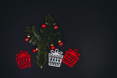 Christmas tree and gifts symbols over black background with fir tree, red christmas balls, top view. Flat inspiring holidays layout.