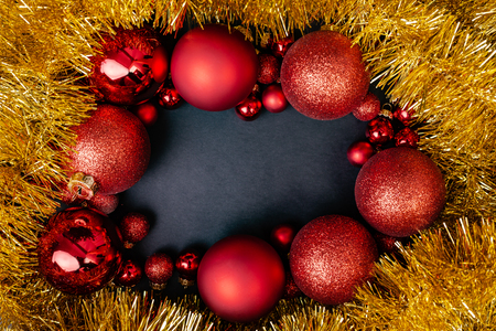 Christmas red balls over black background, red frame with black empty space. Top flat view with copy space.