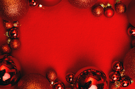Christmas red background with fir tree, red Christmas balls frame. Top flat view with copy space.