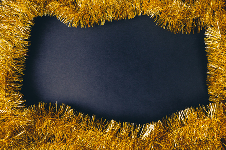 Golden carnival or new year frame over black empty copy space background. Top flat view with dark shadow. Imagens