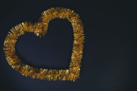 Golden heart shape over black background. Love and carnival concept. Heart frame, top view with copy space.