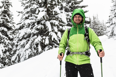 Smiling man walking on winter trek in white snowy forest, looking at camera. Man hiking in winter woods. Travel and healthy lifestyle outdoors in beautiful nature. Imagens