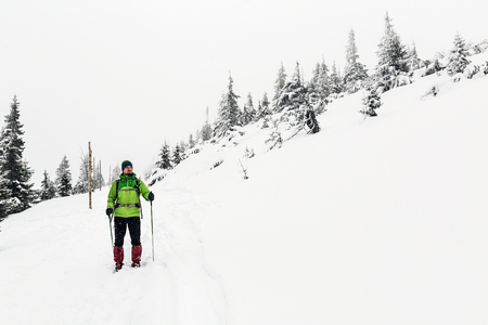 Winter trek in white woods. Man hiking trekking in winter white forest. Travel recreation fitness and healthy lifestyle outdoors in beautiful snowy nature. Motivation and inspirational white winter landscape.