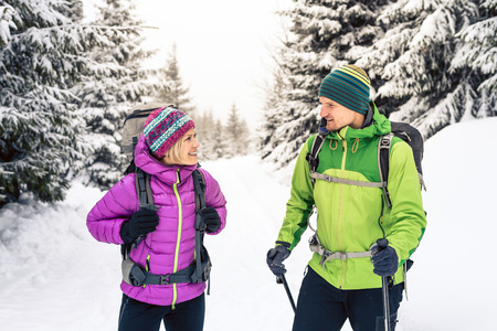 Man and woman happy couple hikers trekking in white winter woods and mountains. Young hiking team, people walking on snow trail with backpacks, adventure and camping on hiking trip, Poland.