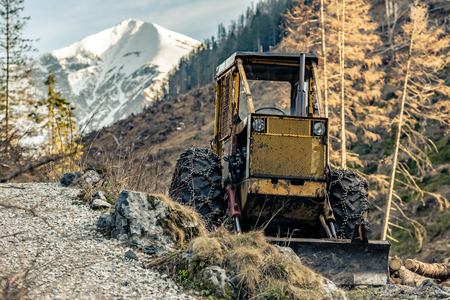 Bulldozer resting in high mountains after work, heavy machinery industry in woods, after work.