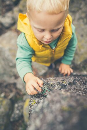 Toddler boy playing with toys on a rock. Little child walking on rocky mountains.