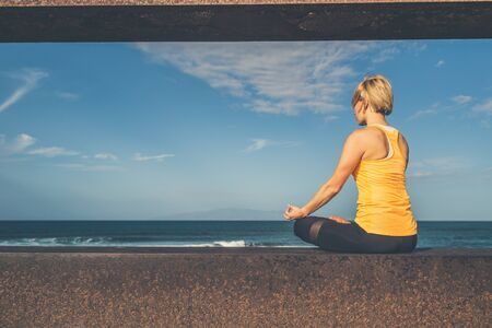 Woman meditating in yoga pose, ocean view, beach and wooden sidewalk. Motivation and inspirational summer sea landscape. Healthy lifestyle outdoors in nature concept.