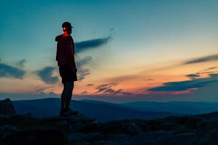 Trail runner with head lamp. Man celebrating sunset on mountain top. Looking at inspiring view. Hiker or climber reached mountain peak, enjoy inspiring landscape on rocky path Karkonosze, Poland Banco de Imagens