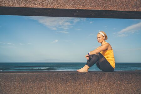 Woman meditating in yoga pose, ocean view. Motivation and inspirational summer sea landscape. Healthy lifestyle outdoors in nature concept.