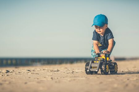 Toddler boy playing with toys on a sunny beach. Little child walking on sand. Beautiful inspirational beach and ocean view, landscape.
