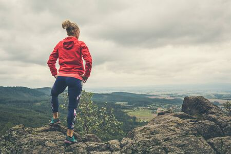 Hiking girl in mountains, looking at view. Travel and healthy lifestyle outdoors in fall season. Looking at mountain landscape.