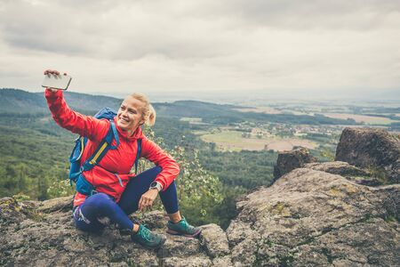 Hiking woman with backpack taking selfie photo with smartphone. Travel and healthy lifestyle outdoors in fall season. Female backpacker tourist photographing landscape.