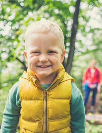 Toddler boy hiking with mother, family adventure. Little child walking in rocky green forest, smiling.
