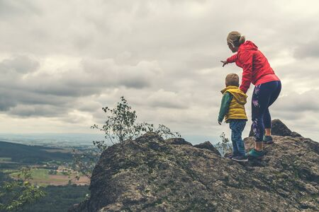 Mother with little boy travelling in mountains. Hiking adventure with child on family trip. Vacations journey with a kid, looking at view. Banco de Imagens