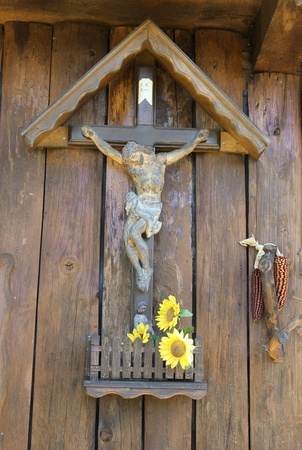 wooden jesus on the cross with statuette and sunflowers Stock Photo