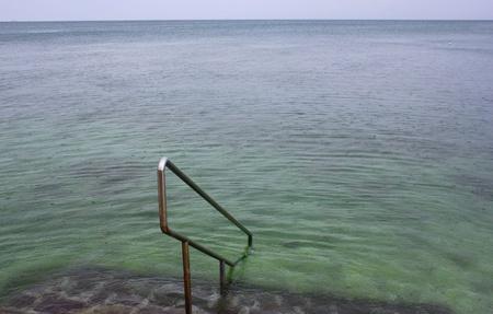 steps into rainy sea in Isola, Slovenia
