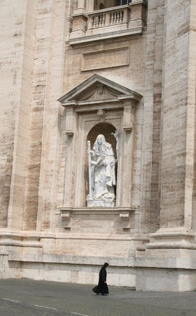 a walking nun and a sculpture on huge wall of the church basilica in the background - Vatican City, Europe Stock Photo