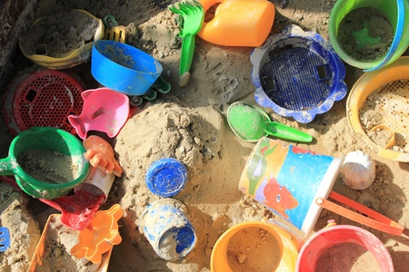 Sandkasten voller Plastikspielzeug in hellen Farben