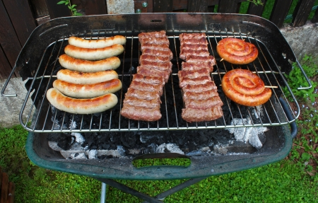 sausages and cevapcici on charcoal barbeque during grilling photo