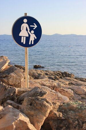 woman and child walking direction - seaside path traffic sign Stock Photo - 14586250