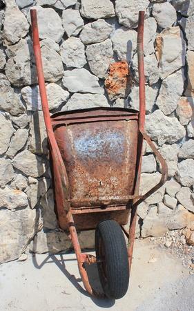 rusty old wheelbarrow on stony wall background - resting in the sun