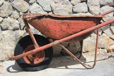 thoroughly used up wheelbarrow on a stony background - poor maintenace andor workaholic treatment Stock Photo