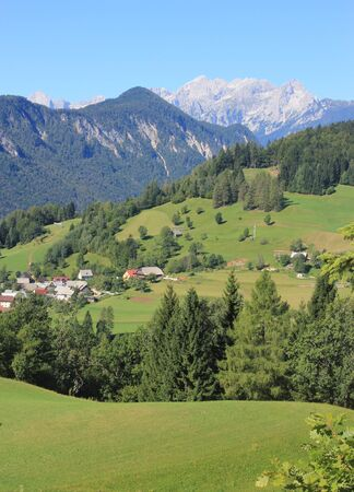 Alpine Landscape - mountain village and Julian Alps in the background, Slovenia
