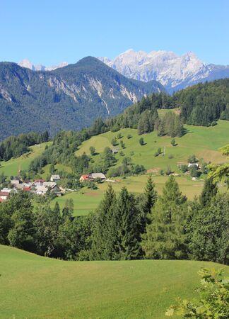 kopi: Alpine Landscape - mountain village and Julian Alps in the background, Slovenia