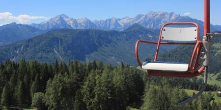 Ski chair lift and panorama of Julian Alps with Triglav, Stenar and Skrlatica mountains - view from Spanov vrh, Karavanke mountains, Slovenia Stock Photo - 17107711