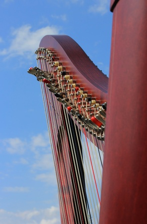 Celtic harp closeup and cloudy sky background  - musical instrument