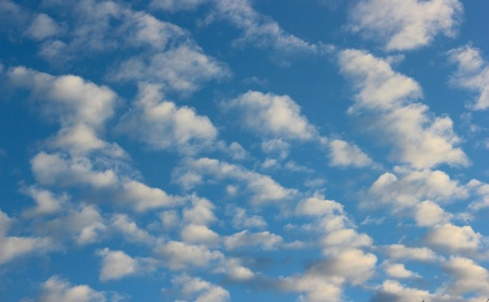 Blue sky with white sheep shaped clouds Stock Photo