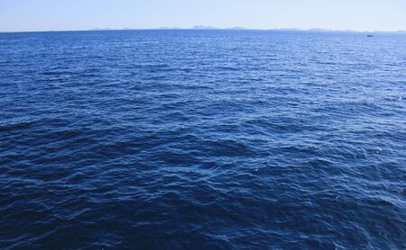 Open blue sea and land on the horizon